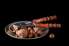 Nuts with nutcrackers on plate, black background. Royalty Free Stock Images
