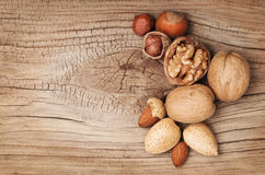 Nuts on old wooden background. Hazelnuts, almonds Royalty Free Stock Image