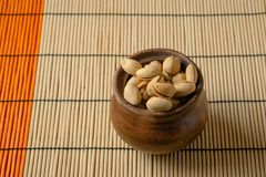 Nuts. Pistachios in a clay bowl on the table. Top view stock images
