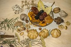 Nuts,pistachios,hazelnuts near a crystal rosette with dried fruit,eclairs on a figured napkin. Nuts,pistachios,hazelnuts near a crystal rosette with dried t Stock Photography