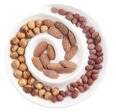 Nuts in a plate. Spiral plate filled with assorted nuts almond, hazelnut and peanut isolated on white with clipping path Stock Photos