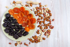 Nuts and plate with dried apricots and prunes on the table Royalty Free Stock Image