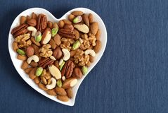 Nuts on a plate in the shape of a heart royalty free stock photos