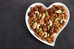 Nuts on a plate in the shape of a heart royalty free stock photo