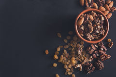 Nuts and raisins at black background. Healthy source of fat for vegans and vegetarians. Nuts and raisins snack at black background. Healthy source of fat for Royalty Free Stock Image