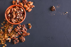 Nuts and raisins at black background. Healthy source of fat for vegans and vegetarians. Nuts and raisins snack at black background. Healthy source of fat for Royalty Free Stock Images