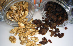 Nuts and raisins. In a glass jar on white table stock image
