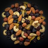 Fruits and nuts. Cashews, almonds, hazelnuts and raisins on a black background. Nuts and raisins are laid out in a large circle in the center of a large frame royalty free stock photography