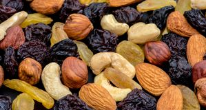 Fruits and nuts. Cashews, almonds, hazelnuts and raisins on a black background. Nuts and raisins are laid out in a large circle in the center of a large frame stock photo