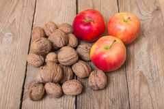 Nuts and red yellow apples on a wooden background Royalty Free Stock Photos