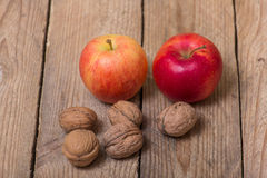 Nuts and red yellow apples on a wooden background Stock Photo
