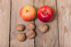 Nuts and red yellow apples on a wooden background Stock Photos