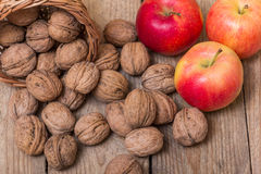 Nuts and red yellow apples on a wooden background Royalty Free Stock Image