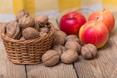 Nuts and red yellow apples on a wooden background Stock Photography