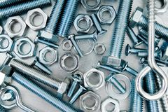 Nuts, screws and bolts on scratched metal Stock Photo