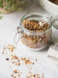 Nuts, seeds, goji berries granola in open glass jar. Healthy breakfast - homemade granola in a jar on a marble white background. Nuts, seeds, goji berries royalty free stock photos
