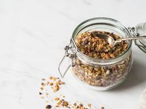 Nuts, seeds, goji berries granola in open glass jar. Healthy breakfast - homemade granola in a jar on a marble white background. Nuts, seeds, goji berries royalty free stock image