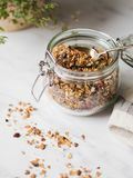 Nuts, seeds, goji berries granola in open glass jar. Healthy breakfast - homemade granola in a jar on a marble white background. Nuts, seeds, goji berries stock photos