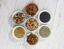 Nuts and seeds. A selection of four different types of nuts and three types of seeds in bowels on a white wooden background Royalty Free Stock Photo