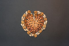 Nuts in the shape of heart. On a black background royalty free stock images