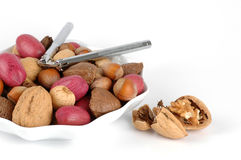 Nuts In The Shell. Bowl of assorted nuts with a nutcracker Stock Photo