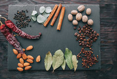 Nuts, spices and food. On a wooden tray Stock Images