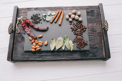 Nuts, spices and food. On a wooden tray Stock Photography