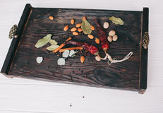 Nuts, spices and food. On a wooden tray Royalty Free Stock Image
