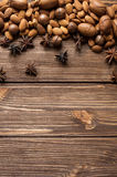 Nuts and star anise on wooden background. Top view. Nuts and star anise on autumn wooden background Royalty Free Stock Photo