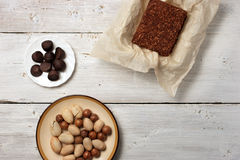 Nuts, truffle candy and chocolate cake on the white background Stock Photo