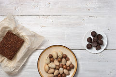 Nuts, truffle candy and chocolate cake on the white background Royalty Free Stock Photo