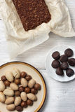Nuts, truffle candy and chocolate cake on the white background Royalty Free Stock Image
