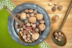 Nuts of various types on a metal plate, from above on a wooden board. Walnuts, hazelnuts and pistachios - various kinds of nuts on a metal plate. from above, in royalty free stock image