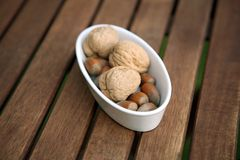 Nuts in white bowl on table Stock Photos