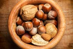 Nuts in a wooden bowl. Walnuts, hazelnuts, almonds in a wooden bowl Royalty Free Stock Photography
