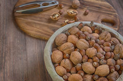 Nutscracker and nuts. Hazelnuts, walnuts and nutcracker on the wooden backgraund Royalty Free Stock Photos