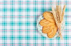 Nuttige graangewassenkoekjes en tarweoren op een geruit tafelkleed Huisontbijt Stock Foto's