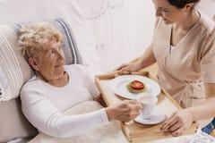 Nuttige vrijwilliger in beige eenvormige dienende koffie aan hogere vrouwelijke patiënt stock foto's