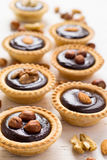 Nutty chocolate dessert small tarts on a white background Stock Photography