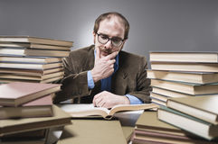 Nutty Professor in between a stack of books. A professor reading books royalty free stock image