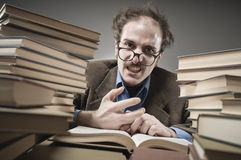 Nutty Professor in between a stack of books. A professor reading books stock image