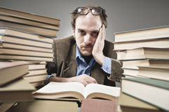 Nutty Professor in between a stack of books. A professor reading books royalty free stock photography