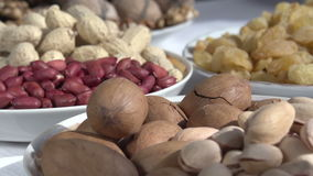 Nutty Snack. Past the camera slowly moving small plates with different kinds of nuts and dried fruits stock video footage