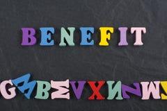 NUTZEN-Wort auf dem schwarzen Bretthintergrund verfasst von den hölzernen Buchstaben des bunten ABC-Alphabetblockes, Kopienraum f Stockbild