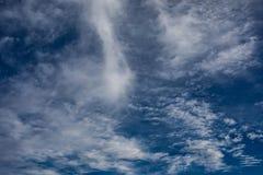 A nuvem branca lista em escuro - fundo azul fotografia de stock