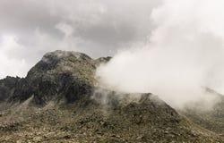 Nuvem dada forma geyser que vem da cratera da montanha imagem de stock