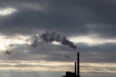 Nuvem de fumo escura pesada da chaminé industrial no por do sol com espaço da cópia imagens de stock