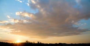 Nuvem grande em um céu azul no alvorecer sobre uma silhueta de uma cidade Fotografia de Stock