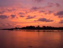 A nuvem vermelha do céu do por do sol reflete no rio Imagens de Stock Royalty Free