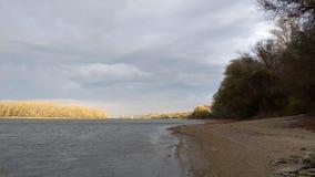 Nuvens acima de uma praia rural no beira-rio imagens de stock